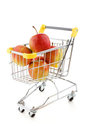 Shopping trolley and apples Stock Photos