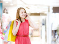 Shopping woman with bags talking on the phone looking away Royalty Free Stock Photo