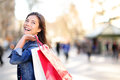 Shopping woman happy and looking away at copy space outdoors shopper girl holding bags up excited outside on walking Royalty Free Stock Photo