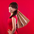 Shopping woman holding bags looking at camera on red background beautiful young asian shopper smiling happy Stock Image