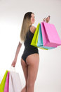 Shopping woman holding shopping bags. Closeup of beautiful women legs in a bathing suit and high heels, holding colorful Royalty Free Stock Photo