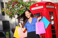 Shopping woman in london walking happy holding bags cheerful beautiful multiracial shopper front of red phone booth Royalty Free Stock Images