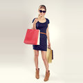 Shopping woman lovely slim lady with full bags beautiful blond caucasian female shopper posing in studio Stock Photo