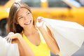 Shopping woman in new york city summer shopper beautiful happy holding bags walking outside smiling with yellow taxi cab Stock Photo