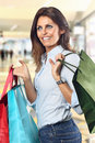 Shopping woman smiles at department store with colorful bags in hands Stock Images