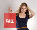 Shopping woman smiling stylish with red bag promoting sale happy young caucasian girl in studio Royalty Free Stock Images