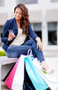 Shopping woman texting on her phone Royalty Free Stock Photos