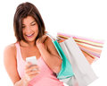 Shopping woman texting on her phone happy cell isolated over white Royalty Free Stock Photography