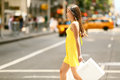 Shopping woman walking outside in new york city holding bags shopper smiling happy crossing the street outdoors while on Royalty Free Stock Images
