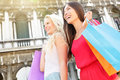 Shopping women happy holding shopping bags venice walking having fun laughing in street beautiful young asian and caucasian Stock Photo