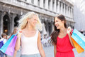 Shopping women happy holding shopping bags venice walking having fun laughing two beautiful young asian and caucasian Royalty Free Stock Image