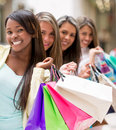 Shopping women in a row at the mall holding bags Stock Photo
