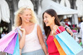 Shopping women two girls shoppers in venice holding bags portrait of beautiful girlfriends smiling happy walking Royalty Free Stock Image