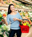 Shopping young girl with a basket full of goods Stock Photo
