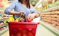 Shopping young girl with a basket full of goods Stock Photos