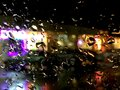 Shops from car window in the rain raindrops on reflecting light Royalty Free Stock Photography