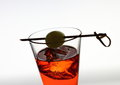 Short drink glass with red liquid, olive, ice cubes Royalty Free Stock Photo