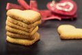 Shortbread cookies in shape of heart as symbol of love over two red hearts background Royalty Free Stock Photography