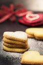 Shortbread cookies in shape of heart as symbol of love over two red hearts background Royalty Free Stock Photos