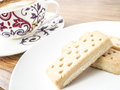Shortbread fingers and coffee on the white plate cup in background Stock Images