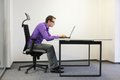 Shortsighted businessman bad sitting posture at laptop Royalty Free Stock Photo