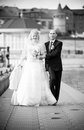 Shot of adult bride and groom walking on pier monochrome Stock Photo