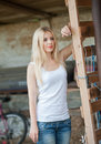 Shot of beautiful girl near an old wooden fence stylish look wear white basic top denim jeans country style farmer long Royalty Free Stock Photo