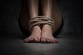 Shot focus of feet of a missing kidnapped abused hostage victim woman tied up with rope in emotional stress and pain afraid Royalty Free Stock Image