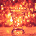 Shot glass of vodka on shiny festive background Stock Photography