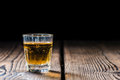 Shot glass with whiskey close up on wooden background Royalty Free Stock Photos