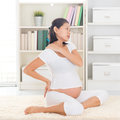 Shoulder and neck pain or eight months pregnant asian woman holding her back while sitting on a floor at home Royalty Free Stock Photography