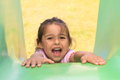 Shouting girl on a slide little with opened mouth sliding down from green Stock Photography
