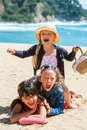 Shouting kids making human pile close up portrait of cute threesome on beach Royalty Free Stock Photography