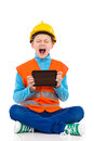 Shouting little construction worker with a digital tablet young boy in yellow hard hat and orange reflective vest holding and full Royalty Free Stock Photo