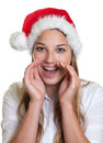 Shouting woman with christmas hat young long blond hair and a funny at camera on a white background Royalty Free Stock Photos