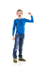 Shouting young boy with arm raised full length studio shot isolated on white Stock Image
