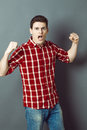 Shouting young man with arms raised expressing his exasperation muscle concept and frustration studio shot low contrast effect Royalty Free Stock Image