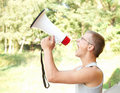 Shouting young man with megaphone Stock Images