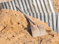Shovel on a heap of sand the old iron with wooden handle lies pile yellow interspersed with gravel construction site against the Royalty Free Stock Photography