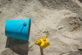 Shovel and pail in sand childs blue pain yellow Royalty Free Stock Photo