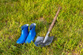 Shovel and rubber boots. Garden tools on a green lawn. Royalty Free Stock Photo