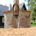Shovel and sand for construction pile against the house Stock Image