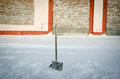 Shovel in snowdrift on a background of a brick wall Stock Images