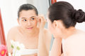 After shower image of a young girl plucking her eyebrows in front of the mirror Stock Photos