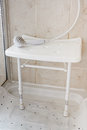 Shower seat white plastic used by the elderly and disabled to aid them by allowing them to sit and wash often reccommended by Royalty Free Stock Photo
