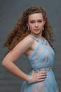 Showing attitude in blue sheer dress upper body view of poised teen with Royalty Free Stock Image