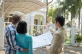 Showing of plan agent a the house to the young couple Stock Photo