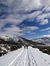 Showshoers  hike up a snow covered road Royalty Free Stock Photo