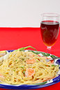 Shrimp alfredo and wine colorful plate of pasta in garlic sauce with glass of dark red on red table Royalty Free Stock Image