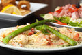 Shrimp scampi with asparagus a delicious pasta dish fried and antipasto salad in the background Stock Photography
